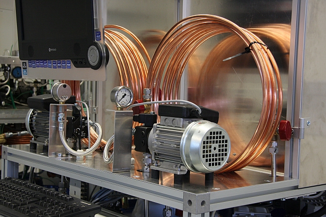 Ein Teststand im Labor mit Kupferleitungen Messuhr, Elektropumpen, Monitor und Tastatur.