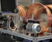 Zwei im Kreis geführte Kupferleitungen, ein Monitor und eine Kraftstoffpumpe auf einem Prüfstand.